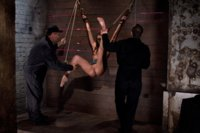Katie Jordin suffers though her first Hogtied bondage scene.  She's suspended by wrists and trapped open against the wall, finger fucked until she squ
