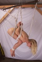 Submissive woman suspended between beams.