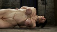Hot busty lifestyle MILF is severely bound with only baling twine!  Bondage hurts, this is brutal. Ass plugged, caned, & hogtied on her poor breasts.