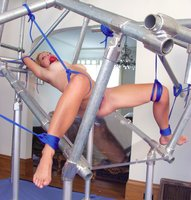 Goldie suspended in a most impressive bondage rack.