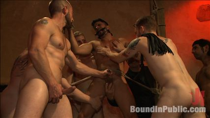 Bound hunk with an uncut dick gets gangfucked by a crowd of excited men. Exciting crowd of men gangbang a latin stud with an uncut cock, covering him in cumshot before tickling the hell out of him!