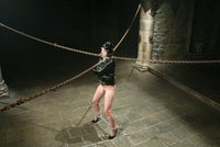 Riped-assed Riley Mason in leather and chains sits on a dildo