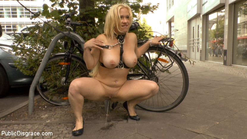 Busty blonde piece of filth begs to be treated like trash. Mona Wales dislikes nothing more than dirty streets and clean submissives. This morning Mona decides to take matters into her own hands and take her lovely blonde ejaculate whore out to clean the streets of Berlin. The site of the humiliated Celina Davis crawling along the sidewalk is a welcome distraction to the morning commuters. Men in suits stop and admire Celina's exposed milky ass, pink cunt and spread asshole. As Mona's human street sweeper crawls to get all the trash, her big tits brush against the filthy sidewalk. Once Mona is satisfied that she has done her public service for the day, she takes Celina's whore holes to be fill at a local bar. Once in the bar Mona opens her slut up to be used. With an ashtray in her mouth Celina's cunt is packed of dick with a double vaginal penetration. After Celina's holes have been completely used up the bar patrons toss their cigaret buts, ash and ejaculate all over her face and perky tits. Thank you Mona for doing your part to make Berlin a cleaner and happier place.