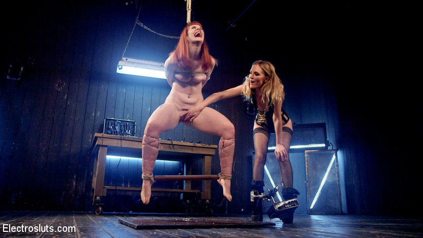 Mona wales ass electrofucks hot redhead barbary rose. Latex domme mona Wales dominates hot redhead Barbary Rose with electro predicament bondage, finger banging, cunt licking, inverted suspension, face sitting, the cattle prod, a wired ass plug, and an booty electrified dildo fucking!