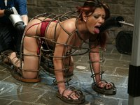 Satine gets machine fucked in a metal cage and cums nonstop.