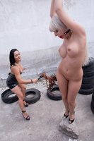 French busty beauty in lesbian bondage outside.