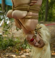 Cowgirl is taken out to the countryside and bound to a tree.