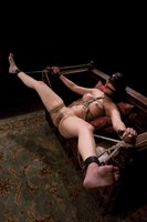 Busty brunette in extreme bondage.