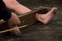 Hot Blond, held in stocks, has her feet tortured, until she begs.