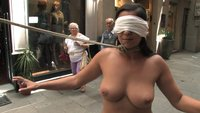 Beautiful brunette is blindfolded and lead fully naked through the center of town