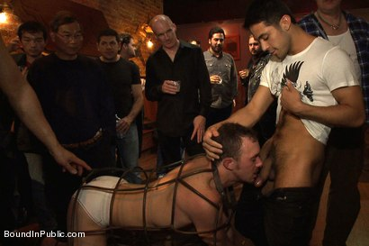 Stud in a metal cage is fucked by horny bar patrons